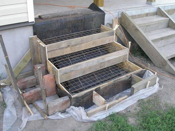 Установка опалубки и армирующего каркаса перед заливкой ступеней бетонного крыльца