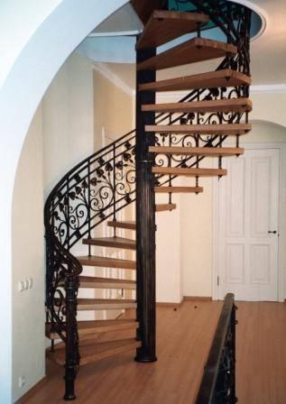 Винтовая кованая лестница с деревянными ступенями
