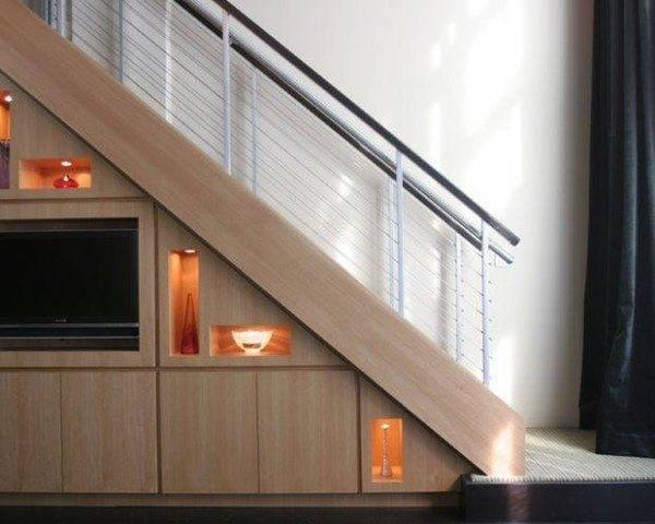 Встроенный телевизор и оригинальные светильники – очень интересное использование пространства под лестницей