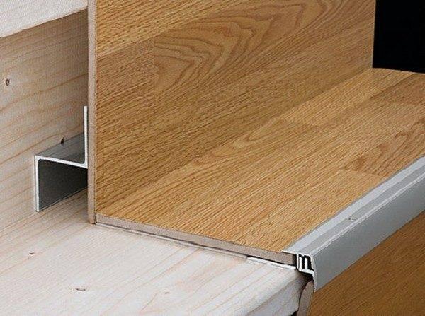 Ламинат для лестниц, по краю которого установлен защитный металлический уголок.
