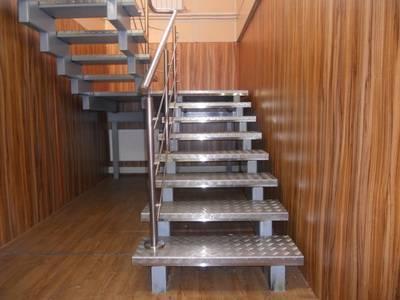 Металлическая лестница в помещении с деревянной отделкой.
