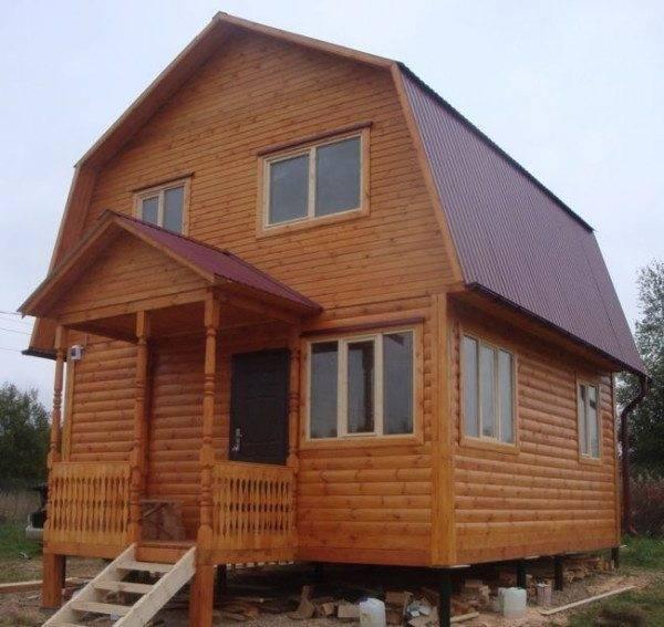 На фото - деревянный дом с крыльцом на столбчатом фундаменте