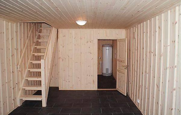 На фото деревянная одномаршевая лестница в комфортное подвальное помещение дома.