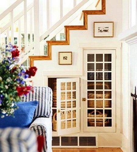 На фото показан вариант, когда пространство под лестницей в прихожей используется в качестве шкафчиков для хранения различных аксессуаров.