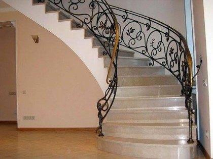 На фото представлена винтовая каменная лестница с коваными перилами.