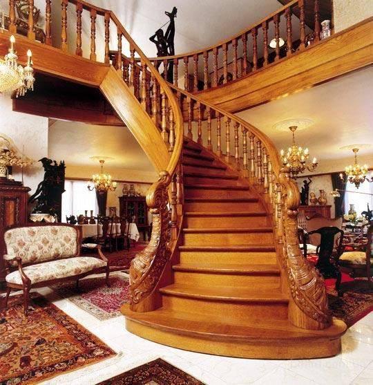 Парадная лестница загородного дома из дерева способна украсить любой интерьер.