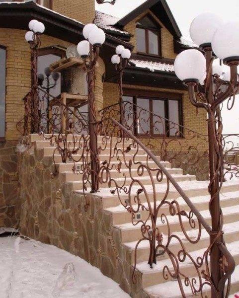 Входная бетонная лестница, отделанная камнем и керамической плиткой.